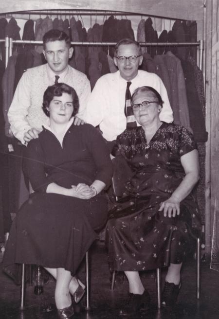 Photo en noir et blanc de deux hommes debout derrière deux femmes, assises sur des chaises. Le couple de droite semble être plus âgé que celui de gauche. Les deux hommes portent des chemises et des cravates et les femmes des robes.