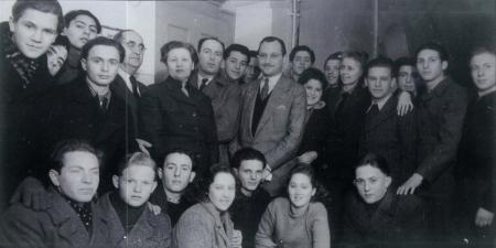 Photo en noir et blanc d'un grand groupe d'environ trente jeunes, rassemblés en deux rangées et souriant à la caméra. Un homme plus âgé portant un complet est debout au centre du groupe.