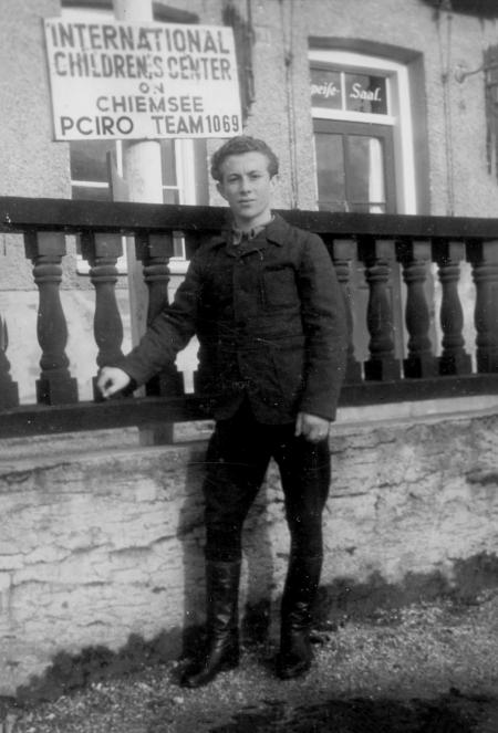 """Photo en noir et blanc d'un jeune homme se tenant sur du gazon à l'extérieur et s'appuyant sur une balustrade surélevée en bois qui est derrière lui. Une affiche en arrière-plan inique """"INTERNATIONAL CHILDRENS CENTRE""""."""