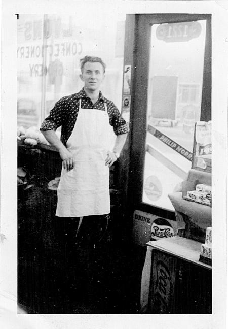 """Photo en noir et blanc d'un homme se tenant à l'intérieur d'une épicerie. Il a les mains appuyées sur ses hanches et il porte un tablier blanc, il est debout près de la porte d'entrée du commerce. Il y a les mots """"LYONS CONFECTIONARY STORE"""" écrits à l'envers dans la fenêtre derrière lui."""