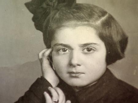 Portrait photographique d'un jeune fille regardant la caméra. Elle a la tête appuyée sur sa main et elle porte une boucle dans ses cheveux bruns courts.