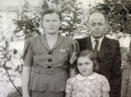 Photo en nir et blanc d'un homme et d'une femme avec leur jeune fille se tenant à l'extérieur où il y a des arbres en arrière-plan. L'homme porte un complet et la femme ainsi que la femme portent des blouses.