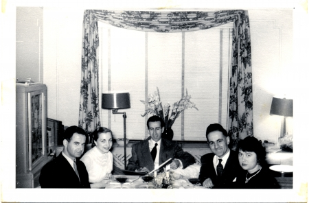 Black-and-white photograph of a group of 5 adults casually sitting at a dining table with glasses of wine, smiling at the camera. The men wear suits.