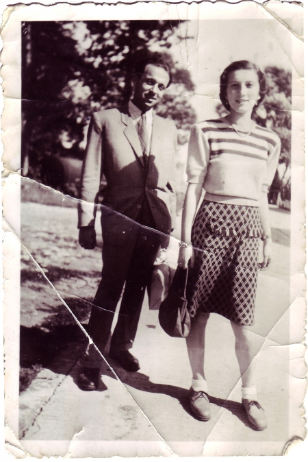 Black-and-white photograph of a man and woman standing together outdoors on the pavement, with trees in the background. The man wears a suit, and the woman wears a blouse and polka-dot skirt.
