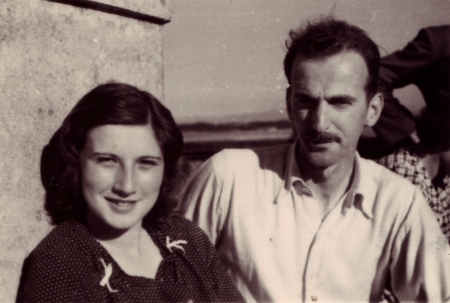 Black-and-white photograph of a man and woman, sitting together outdoors. The woman has shoulder-length brown hair, and the man has a moustache, wearing a light collared shirt.