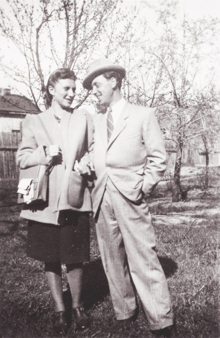 Black-and-white photograph of a man and woman, standing together, arm-in-arm, in a field outdoors with trees in the background. The couple smiles at one another and the man wears a hat and suit.