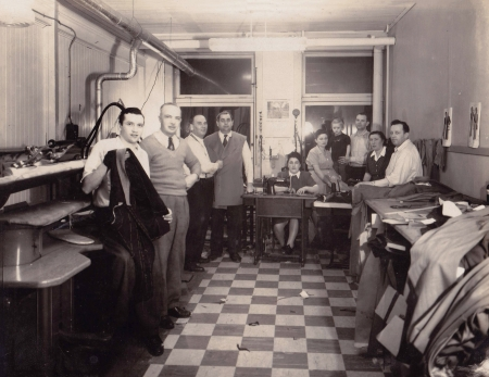 Black-and-white photograph of a group of about ten people standing or sitting together in a room with two windows at the back. The group looks at the camera. Piles of fabric and clothing are on the right, and the floor is checkered.