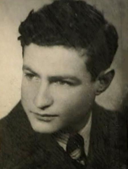 Photo en noir et blanc du profil d'un jeune homme, regardant vers la gauche de la caméra. il porte un complet et a des cheveux bruns foncés bouclés.