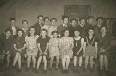 Photo en noir et blan d'un groupe de classe, rassemblé en deux rangées chaque d'environ 10 à 12 enfants. Les filles portent des robes, assises dans le premier rang, et les garçons sont debout derrière elles et portent des chemises à col.