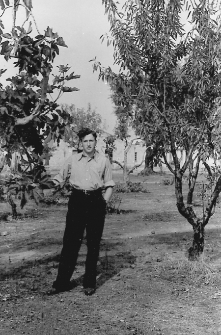 Black-and-white photograph of a young man standing on a lawn, with a tree on either side of him. He has his hands in his pockets, and wears dark trousers and a light collared shirt.
