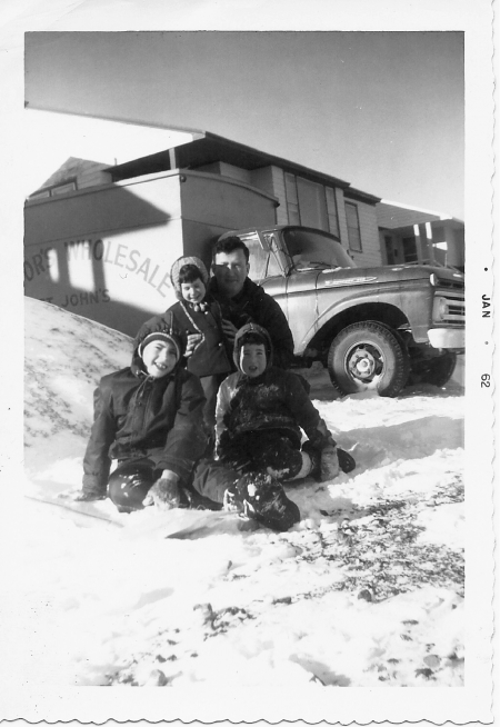 Black-and-white photograph of man with his three young children, sitting in the snow outdoors. They smile at the camera, grouped together in front of a house with a truck in the background.