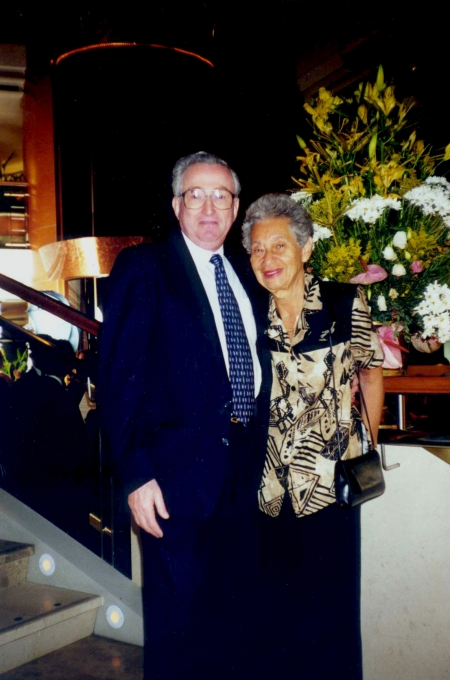 Colour photograph of an elderly couple standing and smiling together, arm-in-arm. The man wears a suit, and the woman wears a printed blouse. They stand in front of a large arrangement of flowers.
