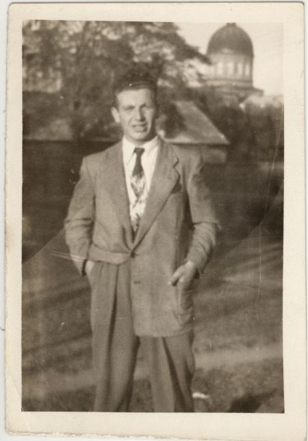 Photo en noir et blanc d'un homme portant un complet et une cravate, debout sur un terrain extérieur. Une tour d'immeuble est visible en arrière-plan.