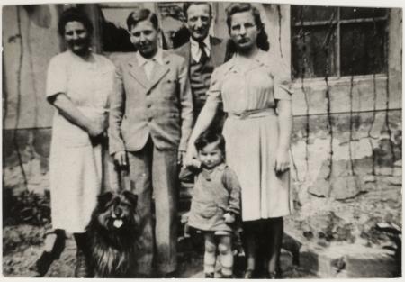 Photo en noir et blanc d'un homme et d'une femme debout à l'extérieur d'une maison avec deux adolescents, un jeune enfant et un chien.