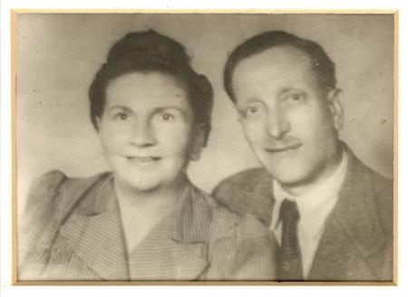 Photo en noir et blanc prise à partir du buste, d'un homme et d'une femme souriant à la caméra. L'homme porte costume et cravate et la femme a les cheveux attachés.