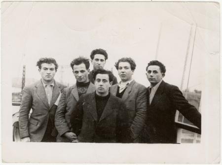 Photo en noir et blanc d'un groupe de six jeunes hommes habillés de manteaux debout ensemble sur le pont d'un navire.