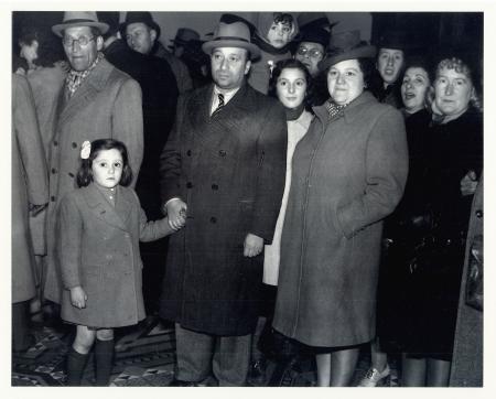 Photo en noir et blanc d'un groupe d'une douzaine de personnes rassemblés ensemble et regardant vers la caméra. Ils portent des manteaux et des chapeaux. L'homme dans la première rangée tient la main d'une jeune fille avec une boucle dans les cheveux.