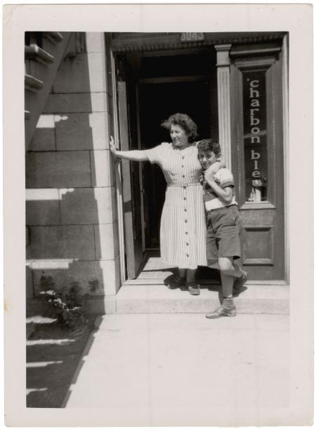 Photo en noir et blanc d'une femme et d'un garçon se tenant debout à la porte d'entrée d'un appartement du rez-de-chaussée. La femme tient son fils d'un bras et s'appuie sur le cadre de la porte de l'autre.