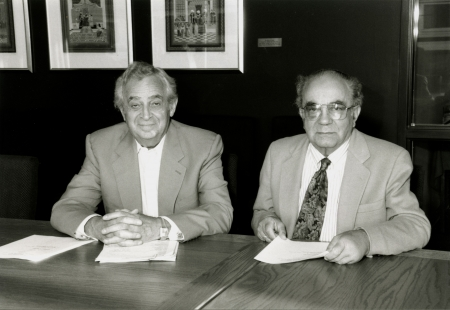 Photo en noir et blanc de deux hommes âgés assis ensemble à une table avec des papiers devant eux. Les hommes portent des vestons, l'un d'eux porte une cravate et il y a trois œuvres d'art encadrées et accrochées derrière eux.