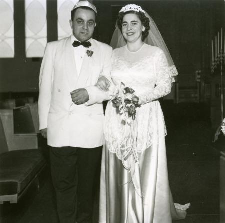 Photo en noir et blanc d'un homme et d'une femme se tenant à l'intérieur bras-dessus bras-dessous. Le couple semble célébrer leur mariage. L'homme porte un complet avec un veston de couleur claire et un nœud papillon, et la femme une longue robe blanche dont la jupe est en soie, un voile et elle tient un bouquet de fleurs.
