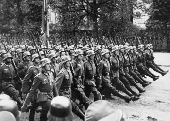 Photo en noir et blanc d'un grand groupe de soldats marchand au même rythme sur un boulevard.