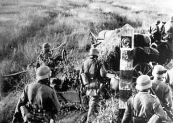 Photo en noir et blanc d'une troupe militaire d'environ une demi-douzaine d'hommes marchant dans un champ. Il semble y avoir un grand feu avec un grand nuage de fumée en arrière-plan.