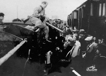 Photo en noir et blanc d'un homme assis sur le bord d'une voiture de train, tenant une canne, et  regardant une plateforme remplie de gens.