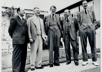 Black-and-white photograph of five men, wearing suits, standing outside in a row and smiling or laughing.