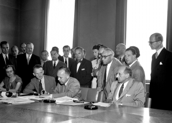 Photo en noir et blanc d'un groupe d'environ 25 personnes rassemblés ensemble derrière une grande table dans une salle de conférence. Quatre hommes sont assis à une table et un homme signe un document. Les autres se tiennent debout derrière.