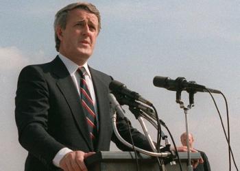 Photo couleur d'un homme en costume, parlant à l'extérieur d'un podium où sont accrochés deux microphones.