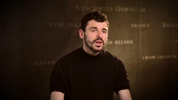 Capture d'écran de l'entrevue d'Antoine Burgard. Il est assis devant un mur gris sur lequel est inscrit les noms de divers camps de concentration. Son visage et ses épaules sont visibles à la caméra.