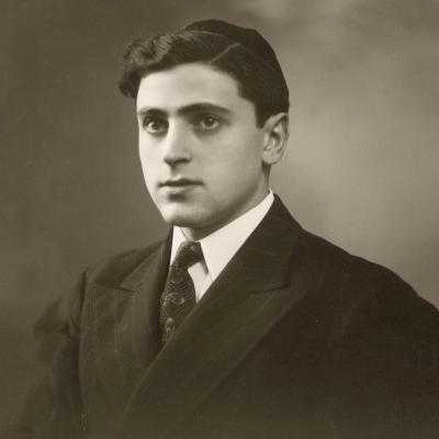 Portrait photographique en noir et blanc d'un homme en costume et cravate, regardant vers la gauche de la caméra. Il porte une kippa sur la tête.
