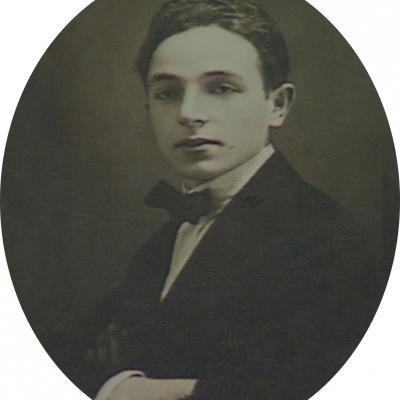 Photo en noir et blanc de forme ovale, prise en studio, d'un jeune homme. L'homme porte un complet avec un nœud papillon. La photo a une grande bordure blanche.