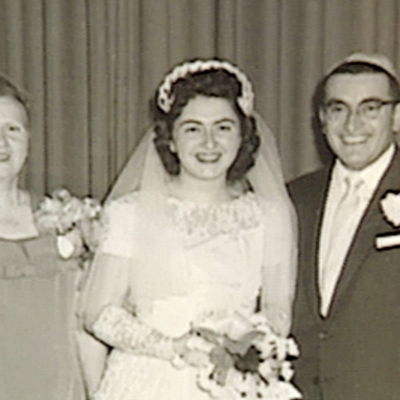 Photo en noir et blanc d'une femme debout et souriant à la caméra pendant son mariage. Elle porte une longue robe blanche, un voile et tient un bouquet de fleurs.