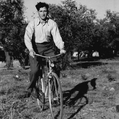 Photo en noir et blanc d'un jeune homme roulant à bicyclette à travers un champ. Il porte des pantalons foncés et une chemise à col de couleur pâle. Il y a des arbres en arrière-plan.