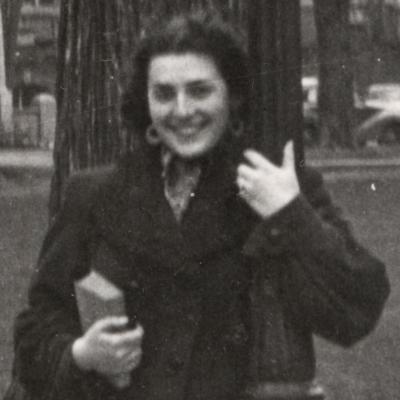 Photo en noir et blanc d'une femme souriant et s'appuyant sur un lampadaire devant un grand champ avec des bâtiments et des voitures en arrière-plan. Elle tient un sac-à-main et un livre dans sa main.