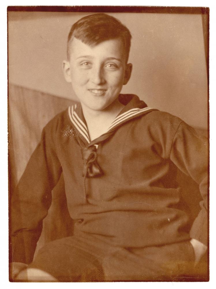 Photo de couleur sépia d'un jeune adolescent assis et souriant à la caméra. Il porte un chandail de couleur foncé avec un col marin.