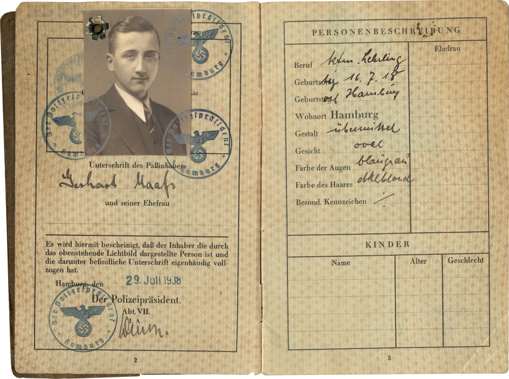 Deux pages d'un passeport avec des estampes bleues et de l'écriture noire. Il y a une photo d'identité en noir et blanc d'un jeune homme portant un costume et une cravate sur la page de gauche.