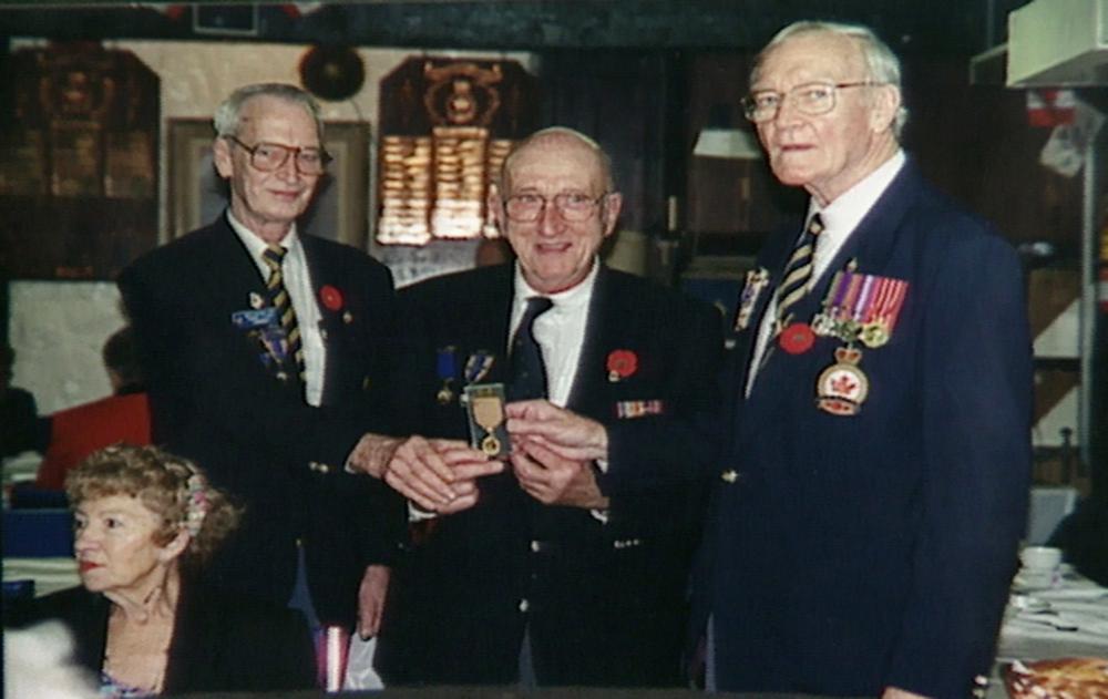 Photo en couleur de trois hommes âgés se tenant debout et tenant  une médaille militaire. Les hommes portent des vestons décorés de médailles et d'épingles.