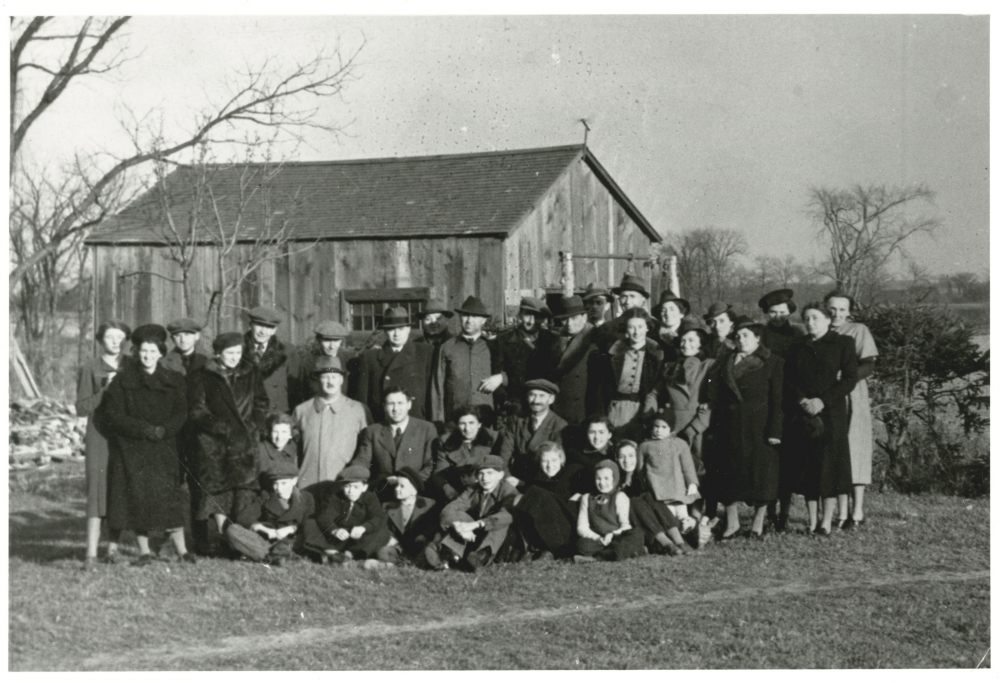 Black-and-white photograph of large group of about 35 men, women, and children, dressed in winter coats and hats, grouped together outdoors on a lawn. There is a barn in the background behind the group.