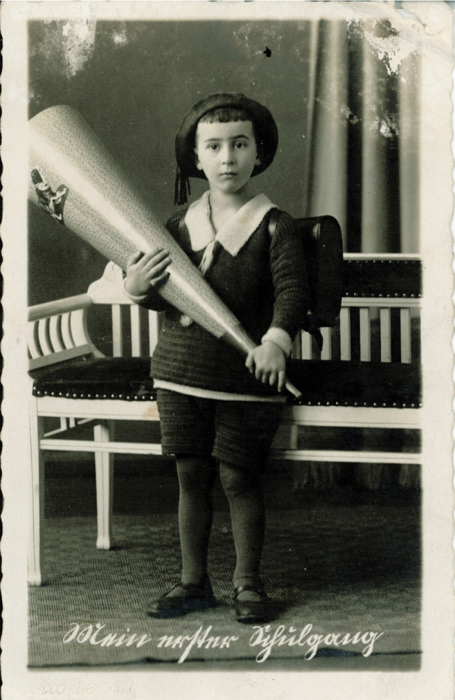 Portrait photographique pris en studio d'un jeune garçon en uniforme et chapeau d'écolier, regardant la caméra en adoptant une pose pensive. Il tient un gros objet ayant la forme d'un cornet. Il y a de l'écriture en allemand au bas de l'image, et les bords de la photo sont usés.