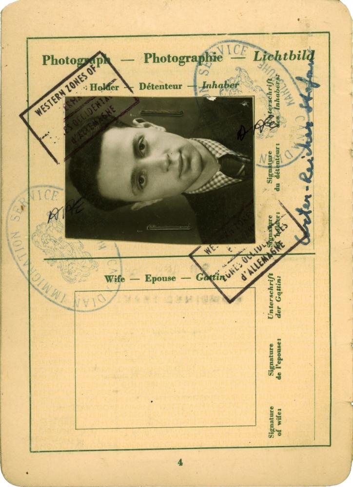 Une page de couleur beige d'un document officiel comprenant plusieurs étampes, des signatures et de l'écriture manuscrite. Sur l'une des pages il y a un portrait en noir et blanc d'un jeune homme les cheveux coiffés vers l'arrière qui porte un complet et une cravate. La photo est placée de côté sur la partie supérieure de la page.