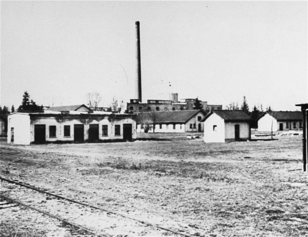 Photo en noir et blanc d'un champ avec des baraquements à un étage et une usine en arrière-plan.