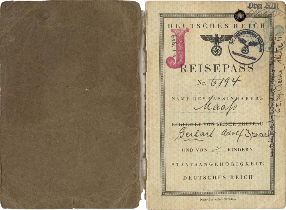 """Photo d'un document brun et beige, rédigé en allemand, incluant une signature manuscrite. La page ouverte a un grand """"J"""" rouge estampé sur le coin supérieur."""
