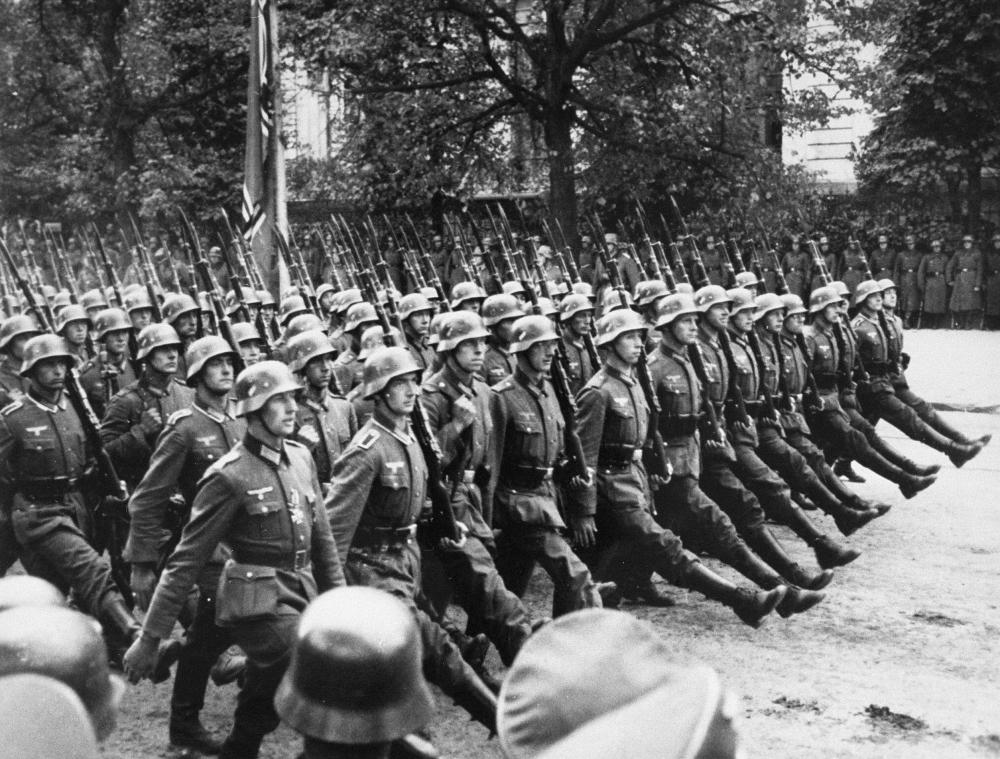 Black-and-white photograph of a large group of soldiers marching in unison on a boulevard.
