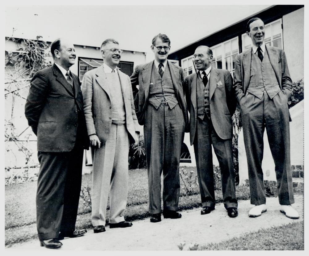Photo en noir et blanc de cinq hommes, portant des costumes et se tenant en rangée à l'extérieure, souriant et riant.