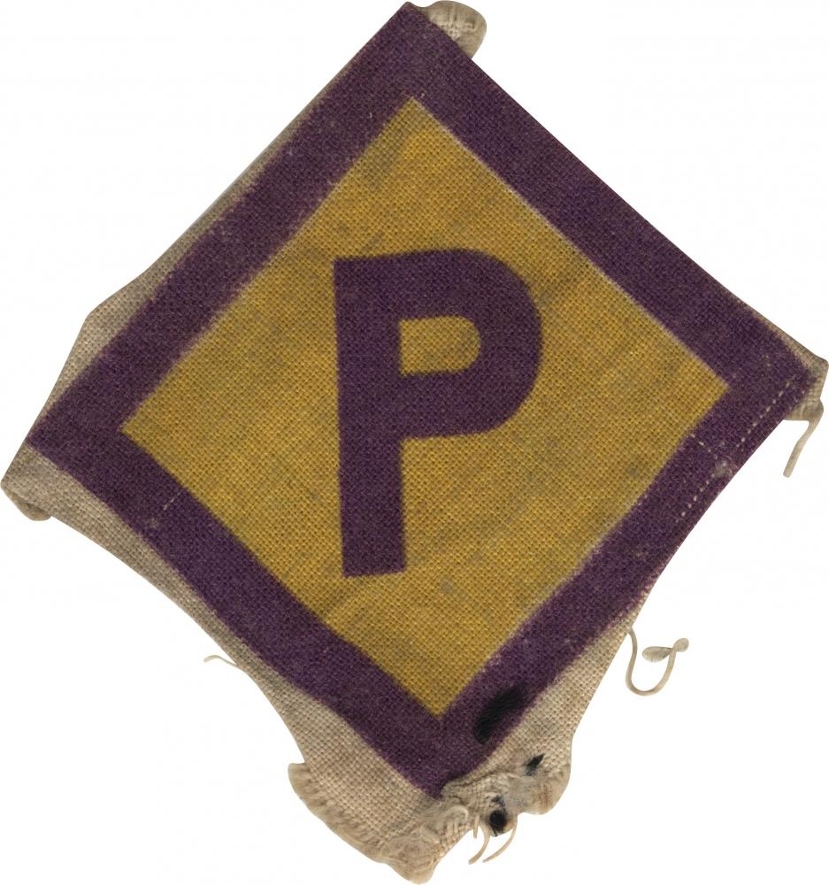 """Photo en couleur d'un badge en tissu en forme de losange. Le centre est jaune avec des bordures de couleur pourpre. Il y a la lettre """"P"""" de couleur pourpre en majuscule au centre du badge."""
