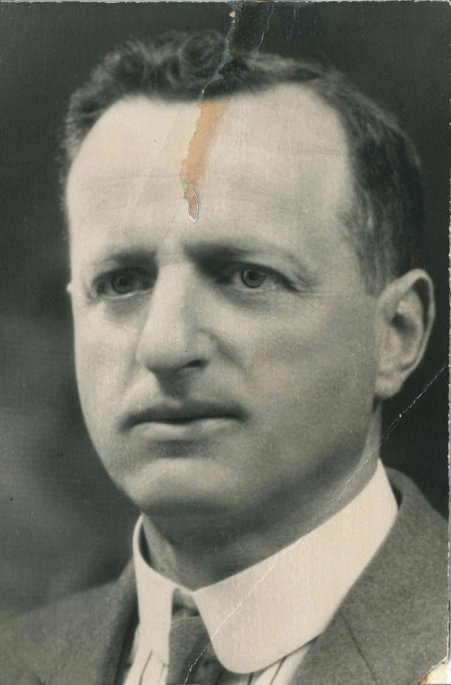 Portrait photographique en noir et blanc d'un homme, la photo est prise des épaules en montant. Il porte un veston et une cravate.