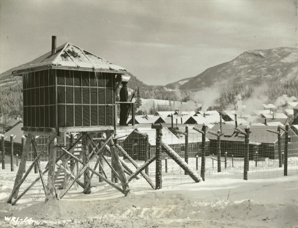 Une photographie en noir et blanc d'un garde qui se tient dans sa caserne entourée de barbelés. Les rangées de bâtiments sont en arrière-plan, avec des collines couvertes de neige au loin. Il y a de la neige au sol.