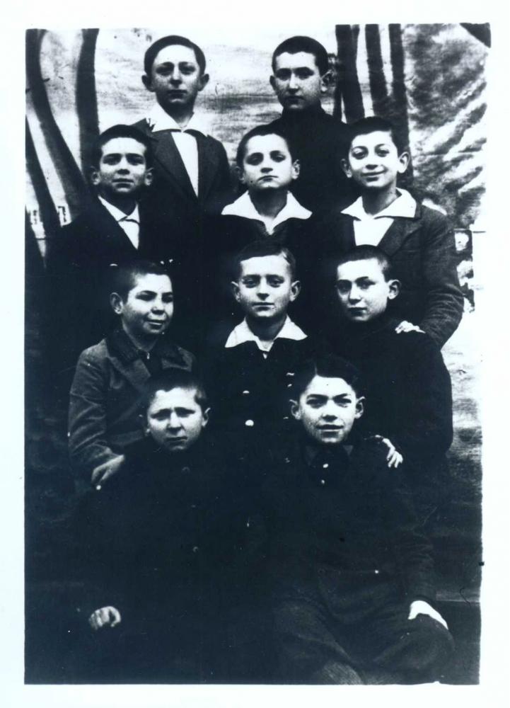 Photo en noir et blanc d'un groupe de dix jeunes garçons, répartis en quatre rangs de deux ou trois. Les garçons regardent la caméra, la plupart d'entre eux portent des chemises à col sous leur veston.
